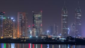 Skyscrapers at the Dubai Internet City illuminated at night timelapse. United Arab Emirates, Middle East. Skyscrapers at the Dubai Internet City illuminated at stock video footage
