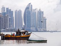 Skyscrapers and fishing boat Stock Photos