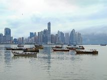 Skyscrapers and fishing boats Stock Image