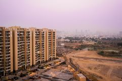 Skyscrapers in gurgaon looking out over barren land and a village. Shows the property and living disparity conditions between rich and poor. Shot at dusk with royalty free stock image