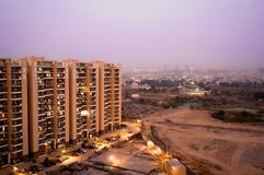 Skyscrapers in gurgaon looking out over barren land and a village. Shows the property and living disparity conditions between rich and poor. Shot at dusk with stock photos