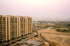 Skyscrapers in gurgaon looking out over barren land and a village. Shows the property and living disparity conditions between rich and poor. Shot at dusk with royalty free stock photography
