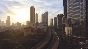 Skyscrapers with highway overpass at sunrise time. JAKARTA - Indonesia. May 21, 2018: Aerial view of skyscrapers with highway overpass in Jakarta at sunrise time Royalty Free Stock Images
