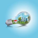 Skyscrapers and house in the light bulb Royalty Free Stock Image