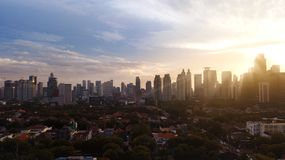 Skyscrapers and residential under light of sunset. Aerial view of beautiful skyscrapers and residential under light of sunset in Jakarta, Indonesia Stock Images
