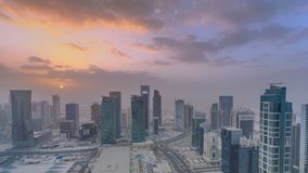 Skyscrapers at sunset timelapse in the skyline of commercial center of Doha, the capital Qatar. Aerial top view at foggy weather. Cloudy orange sky stock video footage