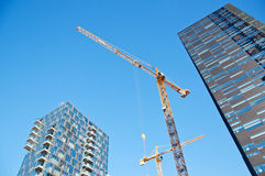 Skyscrapers with tower cranes. On sky background Stock Photos