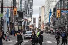 Skyscrapers on Yonge street, on Yonge Dundas Square, with people crossing on a sidewalk, stores and shops stock photo