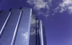 Skyskrapa som reflekterar blå himmel och moln Arkivfoto
