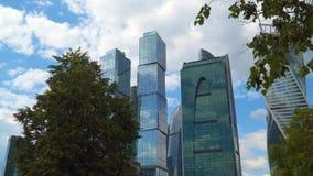 Skyskrapor av affärsmitten beskådar bakifrån trädfilialer