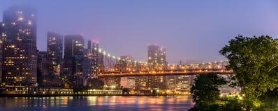 Skyskrapor och bro som är upplysta i afton Arkivbild