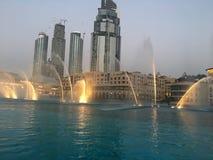 Skyskrapor och de Dubai springbrunnarna i aftonen Royaltyfria Foton