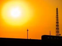 Skytrain als Schattenbild mit schönem goldenem Sonnenlicht und warmem Tonorangenhimmel Stockfoto
