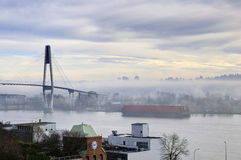 Skytrain bridge and city are shown in a foggy morning Stock Photography