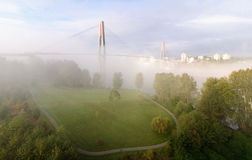 Skytrain bridge by a riverside park in a foggy morning Stock Image