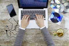 Skytte för ung kvinna från över att arbeta på bärbara datorn på trätabellen som lyssnar till musikCD med en kopp te och en headph royaltyfri bild