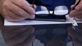 Skytte med affärsmannen Hands Taking Eyeglasses från skrivbordet lager videofilmer