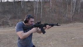 Skytten gör en serie av skott från ett svart anfallgevär på skjutbanan Slapp fokus Kameran är i rörelse stock video