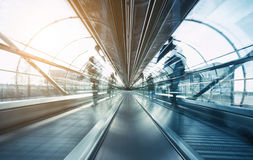 Skywalk futuriste d'aéroport avec les passagers brouillés Photographie stock