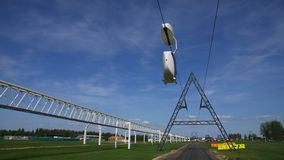 Skyway uniwind moves along string over meadow low angle shot. New skyway uniwind drives along cableway string over green meadow against blue sky on sunny day low stock video