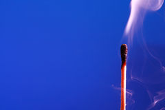Släckt match på blått Arkivfoton
