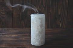 Släckt stor stearinljus i mörkret P? en tr?bakgrund Stearinljusr?k arkivfoto