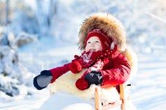Släde- och snögyckel för ungar Behandla som ett barn sledding i vinter parkerar Royaltyfri Foto