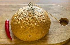 Släntra av bröd med tjänad röd peppar för sädes- amd Royaltyfri Bild