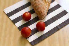 Släntra av bröd och körsbärsröda tomater Royaltyfri Bild