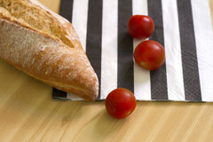 Släntra av bröd och körsbärsröda tomater Arkivfoton