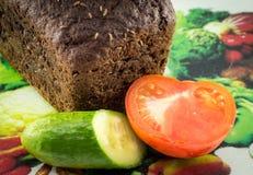 Släntra av bröd och tomaten på en skärbräda Royaltyfri Fotografi