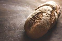 Släntra av bröd på en träbakgrund royaltyfri bild