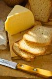 Släntra av hem- bakat Sourdoughbröd som skivas på den Wood skärbrädastora biten av ostknivlinnehandduken royaltyfria foton