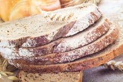 Släntra bröd som skivas med frasiga rullar Royaltyfri Bild