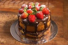 Släntra kakan med chokladsirap med jordgubben arkivbild