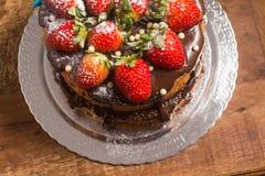 Släntra kakan med chokladsirap med jordgubben royaltyfri foto