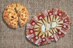 Släntrar den välsmakande maträtten Meze för aptitretaren och sönderriven tunnbröd uppsättningen på den blekte jutekanfasbakgrunde Royaltyfri Bild