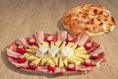 Släntrar den välsmakande maträtten Meze för aptitretaren och tunnbröd Pitta uppsättningen på grov blekt yttersida för jutekanfasG Arkivbild