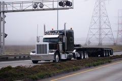 Släpet för plan säng för lastbilen för den ursnygga svarta stora riggen delade den halva vägen Arkivbilder