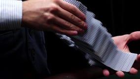 Släpiga kort för croupier under tabellen på kasinot, ultrarapid lager videofilmer