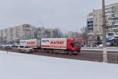 Släplastbilen transporterar produkter på vintervägen till det trad Royaltyfri Fotografi
