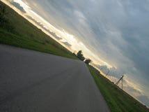 Slät rak asfaltväg i bygden under himlen med moln på solnedgången royaltyfri foto