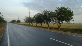 Slät rak asfaltväg utanför staden efter regnet royaltyfria bilder