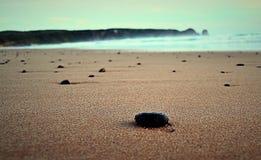 Slät svart sten på sanden vid havet Arkivfoton