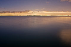 Slät vattenyttersida med avlägsna Melbourne ljus Royaltyfri Fotografi
