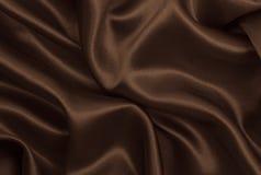 Släta elegant brun silke- eller satängtextur som abstrakt backgroun Arkivbilder