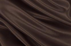Släta elegant brun silke- eller satängtextur som abstrakt backgroun Arkivfoto