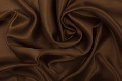 Släta elegant brun silke- eller satängtextur som abstrakt backgroun Royaltyfria Bilder