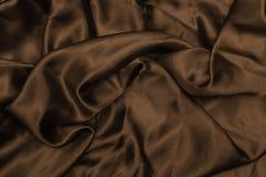 Släta elegant brunt silke, eller satängtextur kan använda som abstrakt bakgrund Lyxig bakgrundsdesigntapet I Arkivfoto
