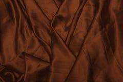 Släta elegant brunt silke, eller satängtextur kan använda som abstrakt bakgrund Lyxig bakgrundsdesigntapet I Royaltyfria Bilder